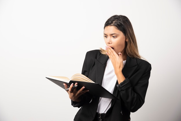 Young businesswoman looking on an opened clipboard with pencil .
