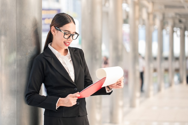 Young businesswoman looking paper board