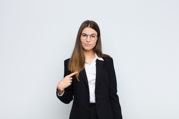 Young businesswoman looking proud, confident and happy, smiling and pointing to self or making number one sign against white wall