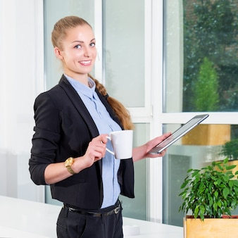 Young businesswoman in modern bright office holding the tablet with a list of tasks and drinking her morning coffee