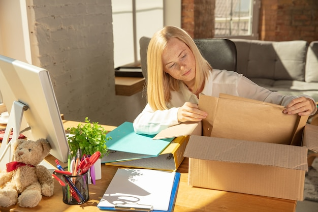 A young businesswoman moving in the office, getting new work place. young caucasian female office worker equips new cabinet after promotion. unpacking boxes. business, lifestyle, new life concept.