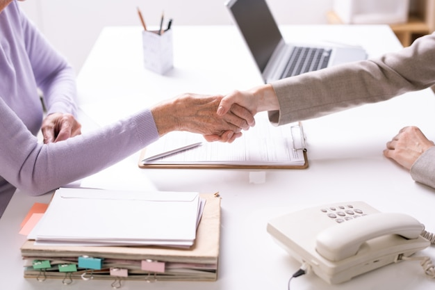 Молодой предприниматель или агент пожимает руку старшему клиенту или партнеру над столом и подписывает документы во время заключения сделки