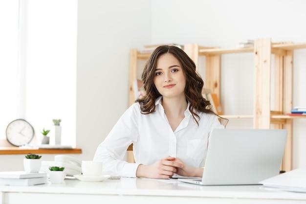 Молодой предприниматель или секретарь сидит за столом и работает, улыбаясь и глядя