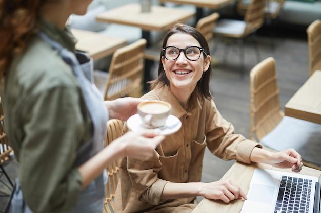 Молодая деловая женщина заказывает кофе в кафе