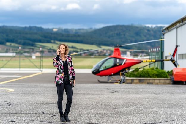 空港で電話をかける若い実業家。ヘリコプターによる輸送