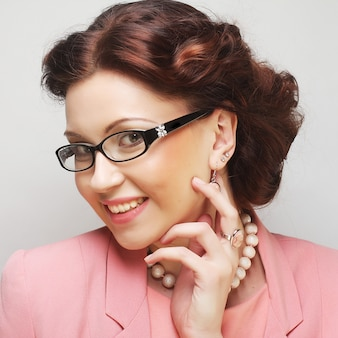 Young businesswoman in pink wearing glasses.
