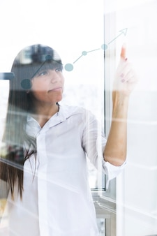 Young businesswoman pointing finger at increasing graph on transparent glass
