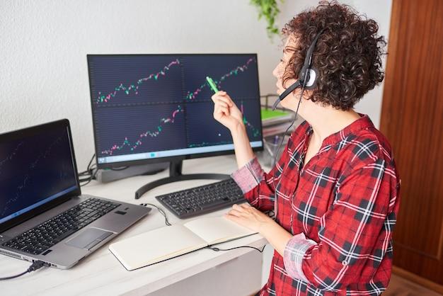Молодой предприниматель указывает на экран компьютера с графиками фондового рынка, нося гарнитуру