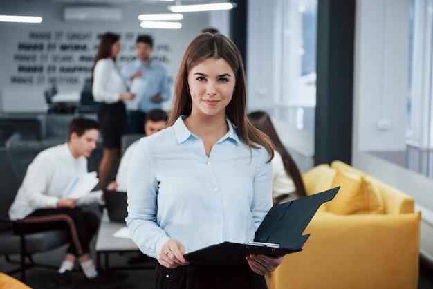 若い実業家。バックグラウンドで従業員とオフィスに立っている若い女の子の肖像画