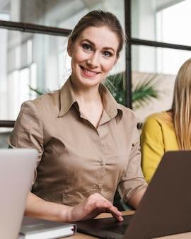 Giovane imprenditrice in posa durante una riunione al chiuso