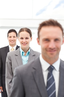 Young businesswoman posing with two businessmen in a row