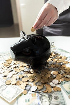 Young businesswoman putting coin in black piggy bank