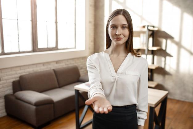 若い実業家がカメラに手を伸ばします。彼女はまっすぐに見えて、少し微笑んでいます。空の部屋。一人で。明け。