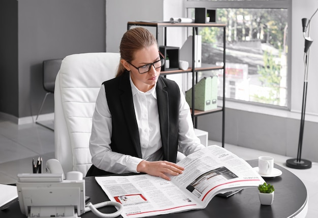 Young businesswoman reading newspaper in office