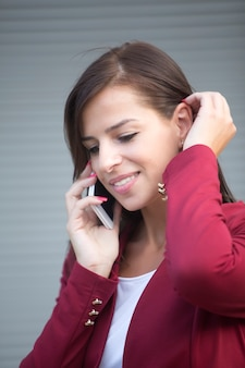 Young businesswoman in red blazer talking over the mobile phone