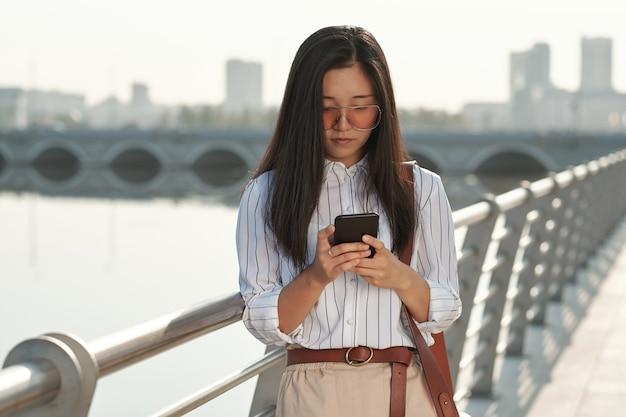 도시 환경에서 스마트폰으로 스크롤하는 젊은 사업가