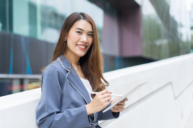 Young businesswoman secretary holding tablet with pen at outside office