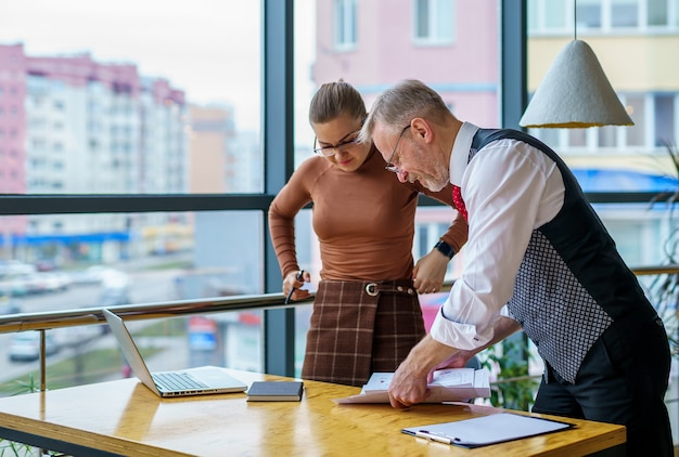 Young businesswoman and senior businessman working together at office, team work.