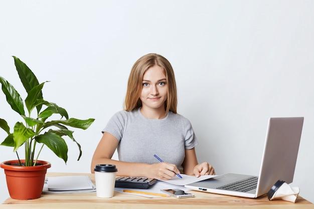 Молодая коммерсантка подписывая документы пока сидящ на таблице на ее рабочем месте