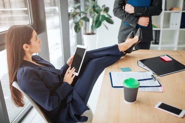 젊은 사업가 방에 창 자에 앉아. 그녀는 테이블에 다리를 잡고 사람을 봅니다. 젊은 남자가 그녀 앞에 서. 모델 홀드 태블릿 및 재생.