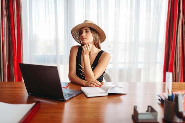 Молодой предприниматель сидит за столом в офисе и мечтает об отпуске