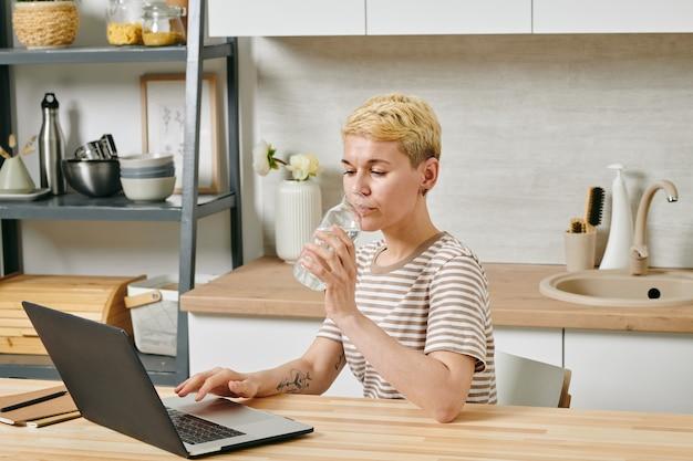 Молодой предприниматель, сидя за столом с ноутбуком и питьевой водой