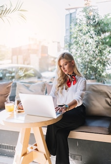 Young businesswoman sitting in the cafe using laptop