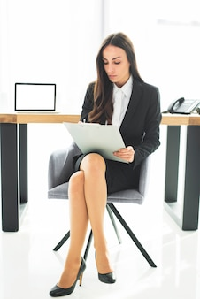 Young businesswoman sitting on chair with crossed legs writing on clipboard