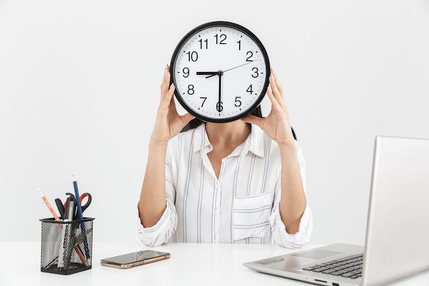 オフィスの肘掛け椅子に座って、白い壁に隔離された彼女の顔の前に大きな時計を保持している若い実業家
