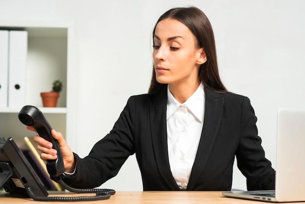 Молодая коммерсантка сидя в офисе устанавливая телефонную трубку