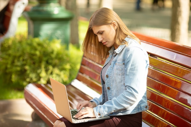 公園に座ってラップトップで作業している若い実業家