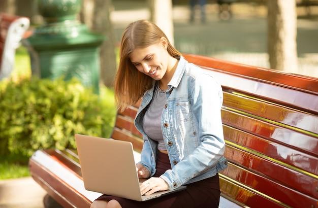 Молодой предприниматель сидит в парке и работает с ноутбуком