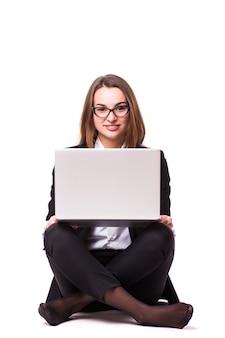床に座って、白い壁で隔離のラップトップを使用して若い実業家