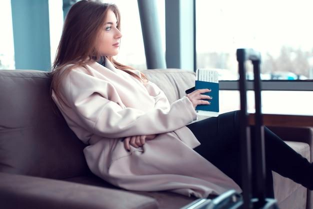 空港の窓の前のソファに座っている若い実業家。バス、鉄道、地下鉄の駅に適しています。