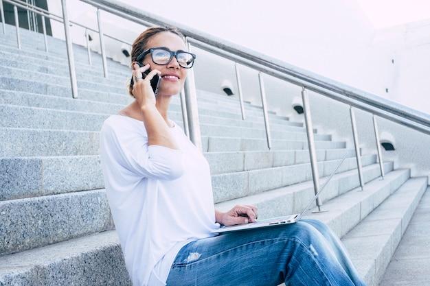 Молодая деловая женщина сидит на открытом воздухе с ноутбуком и телефонными звонками и работает бесплатно в удаленном умном офисе - современные люди и подключение к интернету, образ жизни - женщина, говорящая в камере