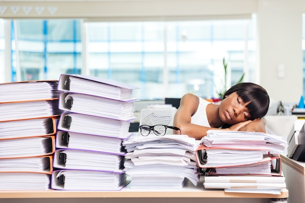 Young businesswoman sleeping on the papers in office