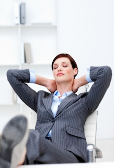 Young businesswoman sleeping with feet on desk