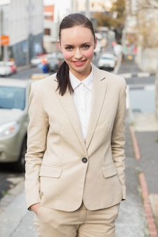 Young businesswoman smiling and walking outside in the city