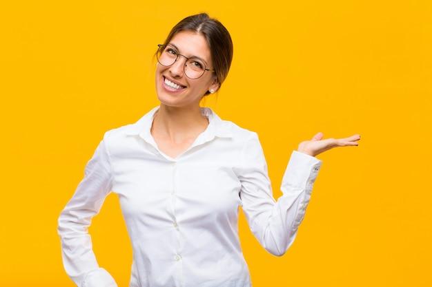 Молодой предприниматель улыбается, чувствуя себя уверенно, успешно и счастливо, показывая что-то