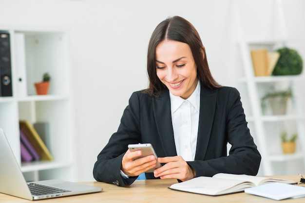 Young businesswoman smiling while looking at smartphone in the office
