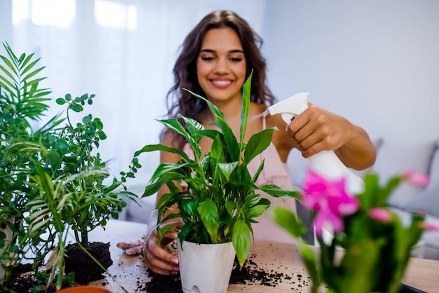 Young businesswoman sprays plants in flowerpots.