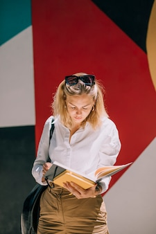 Young businesswoman standing against colored wall reading the book