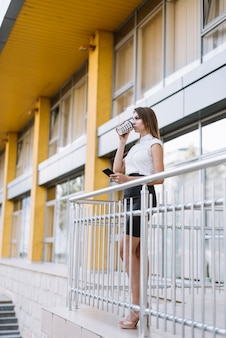 Young businesswoman standing in balcony drinking coffee holding smartphone in hand