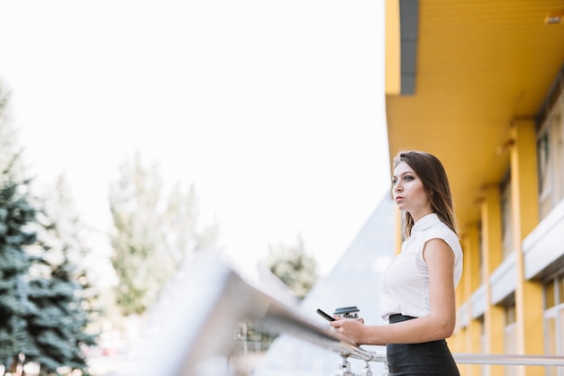 Young businesswoman standing in balcony holding cellphone and disposable coffee cup