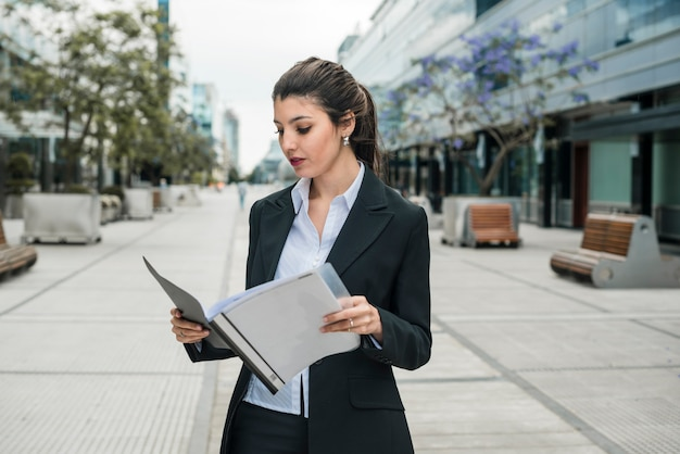 Young businesswoman standing in the business campus reading the folder