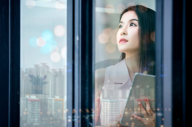 Young businesswoman standing by window while holding tablet and looking outside.