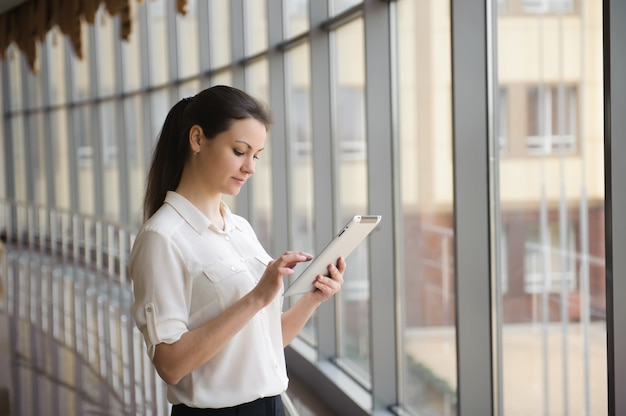 Young businesswoman standing by window with tablet