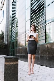 Giovane donna di affari che sta davanti alla costruzione facendo uso del cellulare