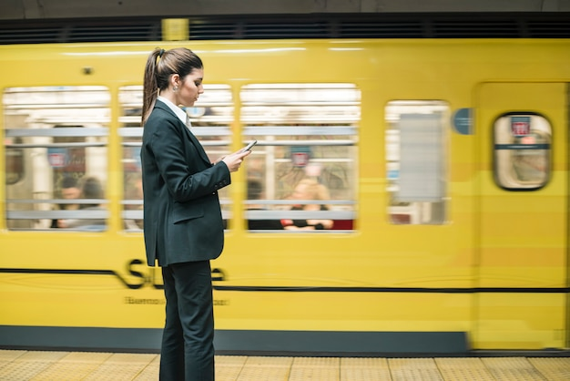 Young businesswoman standing in the front of moving subway train using mobile phone