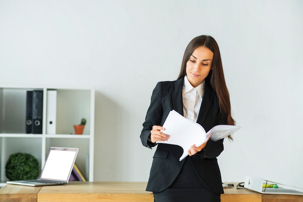 Young businesswoman standing in front of office desk reading documents